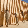 100301-N-4440L-196 HELMAND PROVINCE, Afghanistan (March 1, 2010) Seabees assigned to Naval Mobile Construction Battalion (NMCB) 74 and NMCB-4 raise a 12-foot wall section for a southwest Asia hut into position at Camp Leatherneck, Afghanistan.  NMCB-74 and NMCB-4 are deployed to Afghanistan providing construction support for Operation Enduring Freedom. (U.S. Navy photo by Mass Communication Specialist 2nd Class Michael Lindsey/Released)